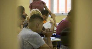 alunos de uma etec vistos em sala de aula através de janela de vidro em porta
