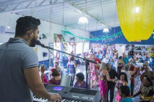 músico tocando teclado diante de grande público dançante da terceira idade