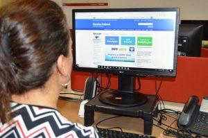uma mulher observando uma tela de computador com o sistema do imposto de renda aberto
