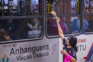 agente de saúde entrega panfleto a passageira de ônibus