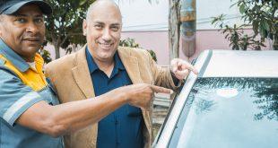 taxista e agente de trânsito posam enquanto afixam selo de aprovação em táxi