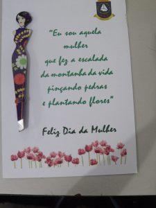 uma pinça em forma de mulher colada em uma folha com os dizeres 'eu sou aquela mulher que fez a escalada da montanha da vida pinçando pedras e plantando flores feliz dia da mulher'