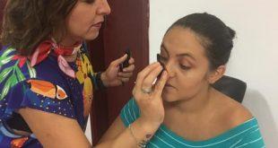 uma mulher sendo maquiada por outra
