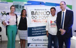 Gilmara Gonçalves, Marcos Neves e outras autoridades posam ao lado de faixa de divulgação do banco do povo