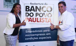 Gilmara Gonçalves e Marcos Neves posam ao lado de faixa de divulgação do banco do povo