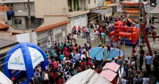 multidão reunida em meio a brinquedos e atividades em rua de carapicuíba