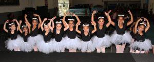 alunas de balé de carapicuíba posam para foto com as mãos levantadas