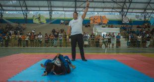 dois atletas no tatame enquanto um árbitro faz orientações
