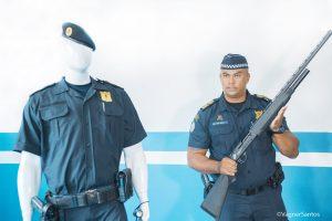 guarda civil posa para foto com espingarda em mãos ao lado de um manequim fardado