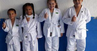 quatro alunos de diferentes tamanhos posam com quimonos novos