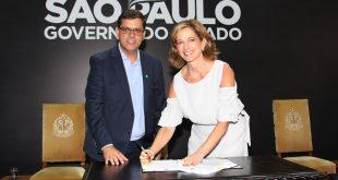 Prefeito Marcos Neves e Secretária Estadual de Desenvolvimento Social Célia Parnes posam para foto enquanto assinam repasse