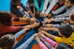 crianças sentadas em círculo com as pernas esticadas e roçando os pés