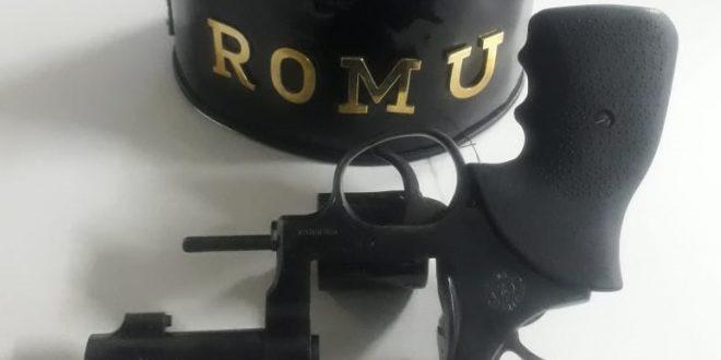 uma arma destravada com cinco balas ao lado e uma braçadeira da romu do outro