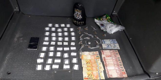 drogas e cédulas de dinheiro dispostos em mesa com bracelete da gcm ao lado