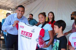 vice prefeitoalmir rodrigues sorri para câmera com camiseta do sesi ao lado de crianças