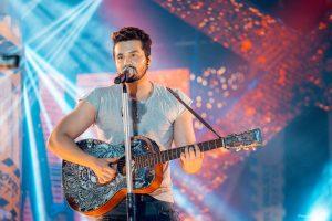 luan santana cantando ao microfone enquanto toca violão
