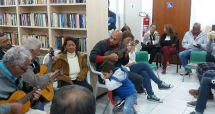 músicos com violão e pessoas sentadas acompanham sarau na biblioteca batista cepelos