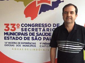 alexandre pierroni posa diante de banner com o logo do congresso