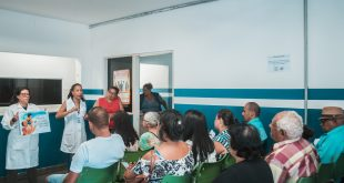 pacientes que aguardam atendimento acompanham esplanações sobre tuberculose dadas por agentes de saúde
