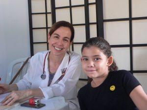 médica e pequena paciente posam para foto