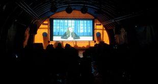 uma tenda arqueada cheia de pessoas vendo um filme projetado numa tela