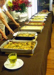 diversas travessas com comidas portuguesas dispostas em uma mesa com mulheres prontas para servir convidados
