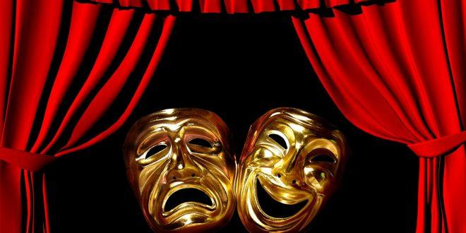 uma máscara alegre e outra feliz ante um fundo preto rodeado por cortinas vermelha de um palco