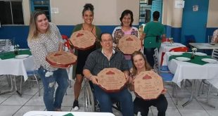 participantes do jantar posam com caixas de pizza em mãos