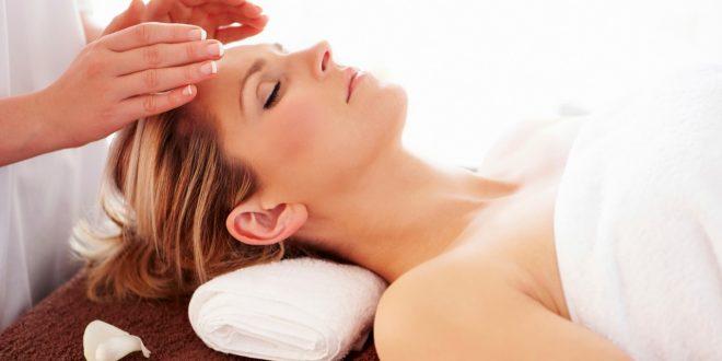 uma mulher deitada e de olhos fechados com um par de mãos sobre sua face realizando um procedimento reiki